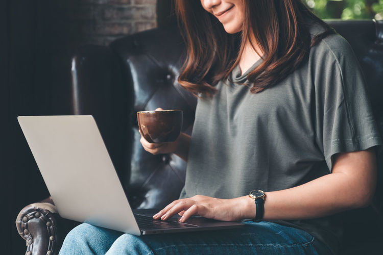 Midsection of businesswoman with laptop having coffee while sitting on armchair
