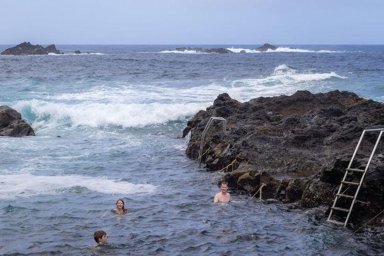 People swimming in natural volcanic thermal sea pool in ponta da ferraria, sao miguel island, azores