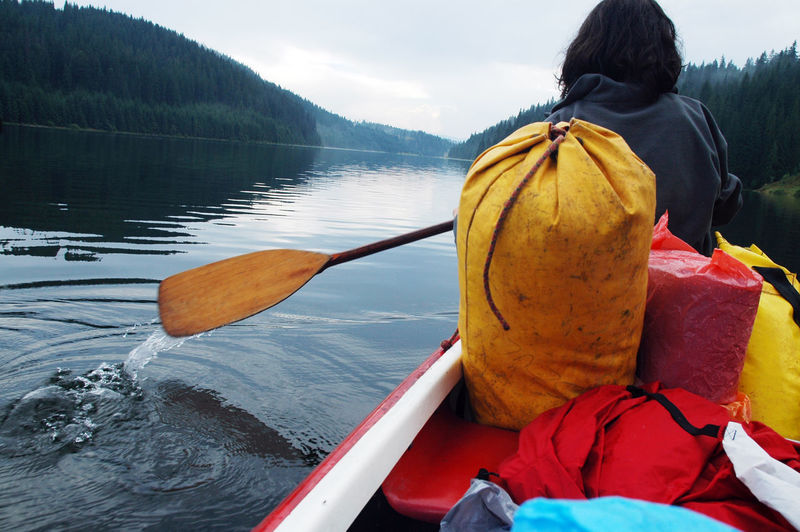 Rear view of woman in boat on lake