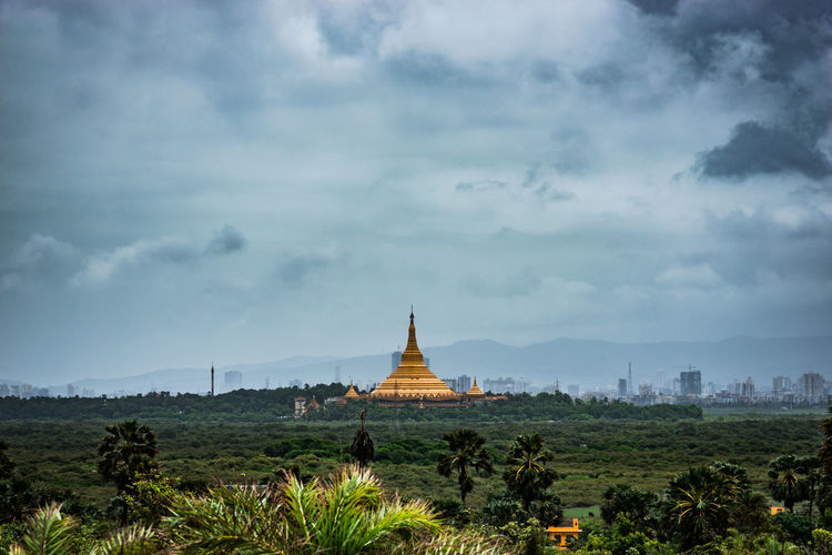 Temple on landscape against cloudy sky