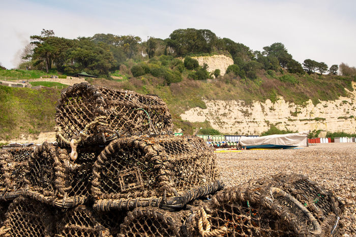 Empty crab pots piled up on a pebble beach with back drop of chalk cliffs, Beer, Devon, UK. Crab Pots Pebble Beach Beach Commercial Fishing Day Fishing Nature Nautical Vessel No People Outdoors Sky Stack Tranquility Tree Water
