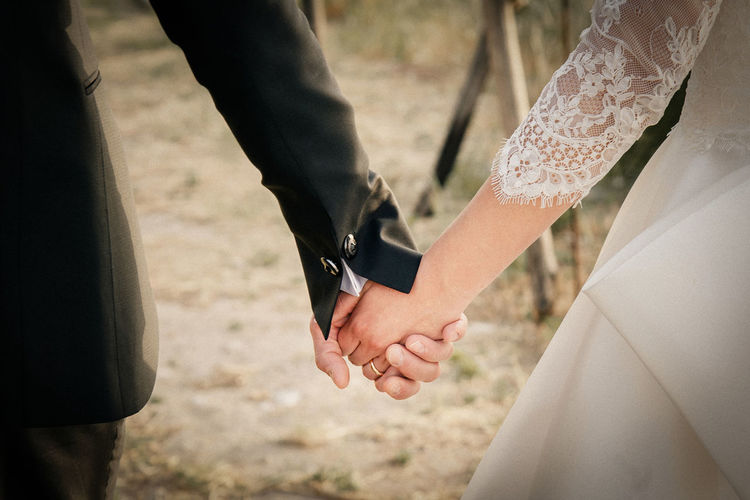 Adult Bonding Bride Couple - Relationship Day Emotion Focus On Foreground Hand Holding Hands Human Hand Love Men Newlywed Outdoors People Positive Emotion Real People Togetherness Two People Wedding Wedding Ceremony Women
