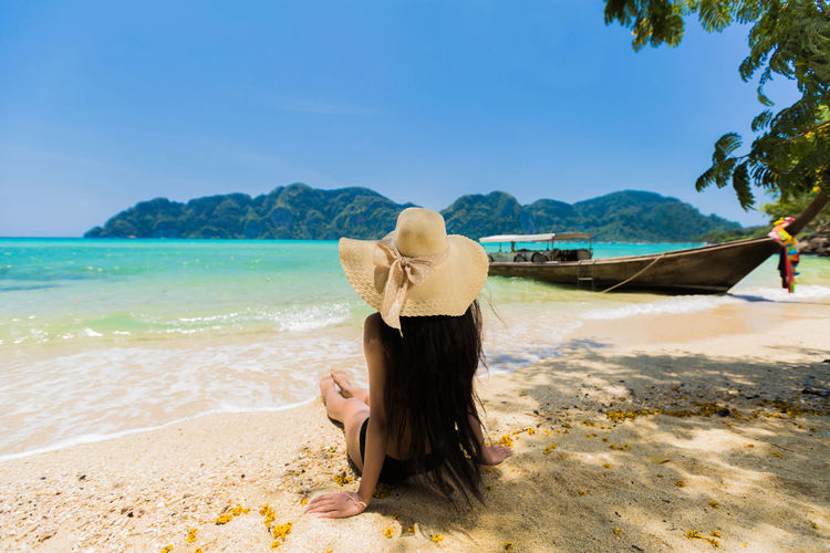 Adult Beach Beauty In Nature Hair Hairstyle Hat Land Leisure Activity Lifestyles Nature Non-urban Scene One Person Outdoors Real People Scenics - Nature Sea Sky Tranquil Scene Tranquility Water Women