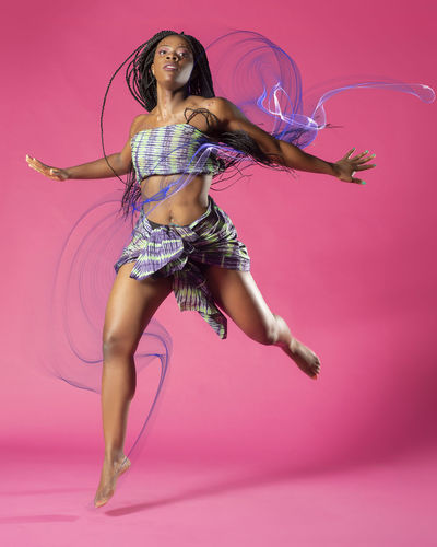 Beautiful African Black girl wearing traditional colorful African outfit does a dramatic dance move against a colorful pink background African African Traditions Adult African Dancer African Woman  Beautiful Woman Beauty Colored Background Dancing Dandelion Fashion Fashion Model Full Length Hair Hairstyle Indoors  Long Hair Motion One Person Pink Color Portrait Studio Shot Tradition Dress Women Young Adult