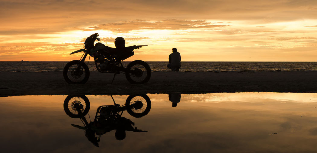 Silhouette of man and motorcycle on beach against sunset sky
