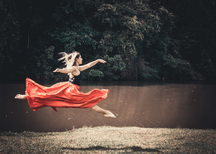 Young ballet dancer wearing red skirt while dancing in forest