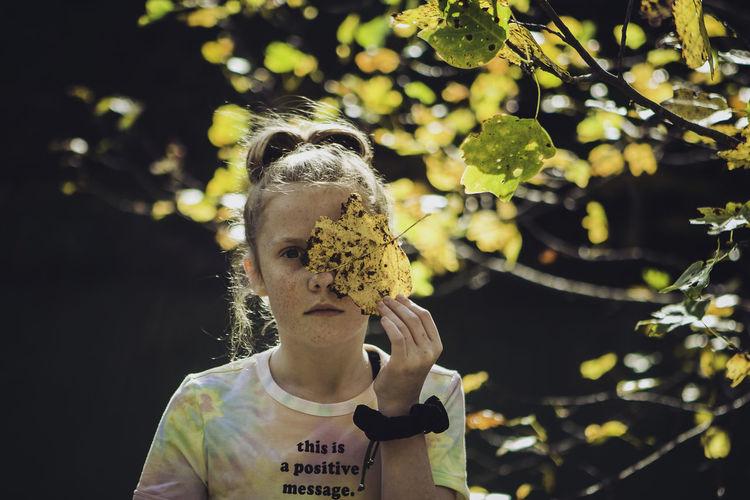 Close-up portrait of a woman holding plant
