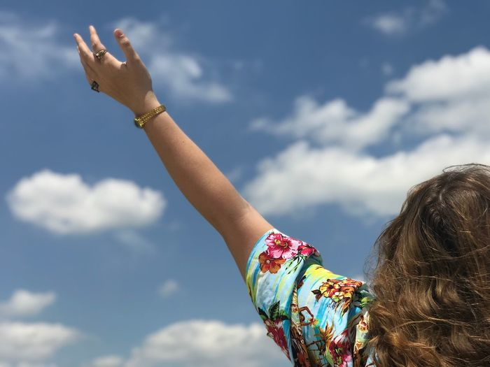 Cropped image of woman hand against sky