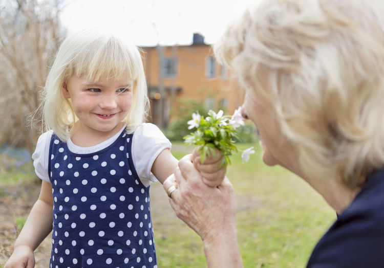 Close-up of a girl holding white flowering plants