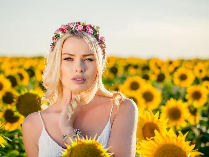 Portrait Of Woman Wearing Wreath Against Sunflower Field