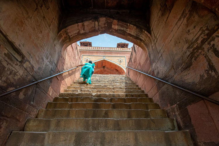 Low angle view of woman moving up on steps at historic building