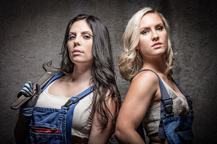 Close-up portrait of female workers standing by wall