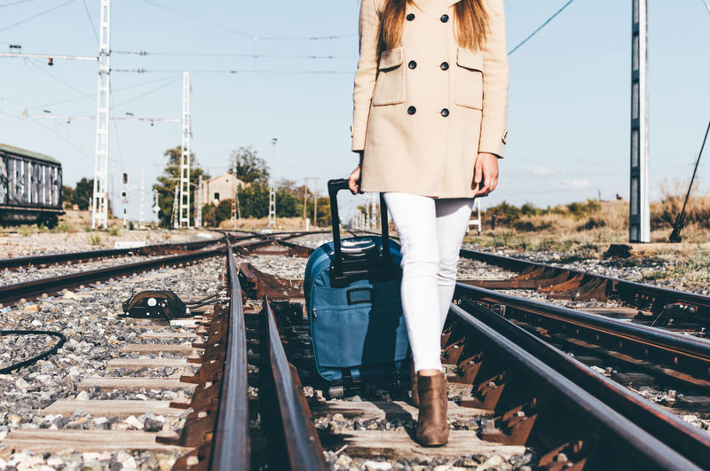 Low section of woman walking on railroad track
