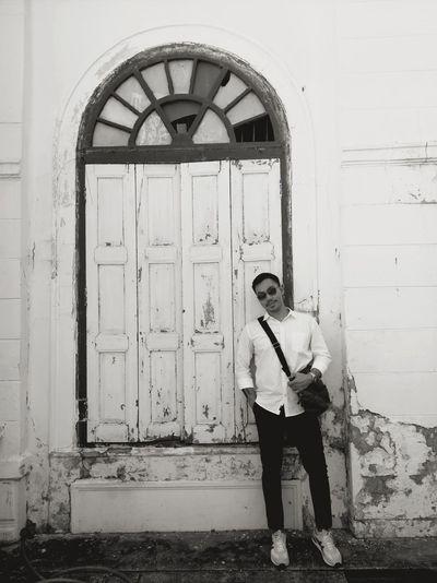 Portrait of mature man wearing sunglasses standing against closed door