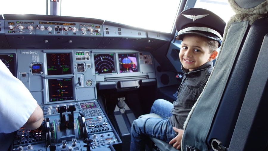 child flight attendant Child Boys Cockpit Piloting Pilot Airplane Technology Air Vehicle Commercial Airplane Headwear Control Panel Occupation