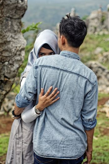 Bandung Shooter Indonesian Shooter Second Acts Arm Around Bonding Casual Clothing Close-up Couple - Relationship Day Embracing Focus On Foreground Leisure Activity Lifestyles Love Men Nature Outdoors People Real People Rear View Standing Togetherness Two People Women Young Adult Young Women