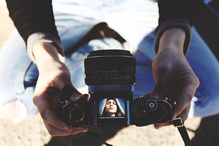 Low section of woman holding camera at beach