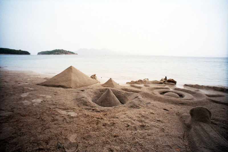 Pyramids made from sand at beach against clear sky