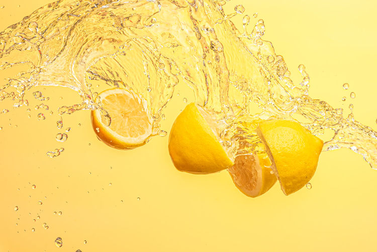 Close-up of bubbles in water against yellow background