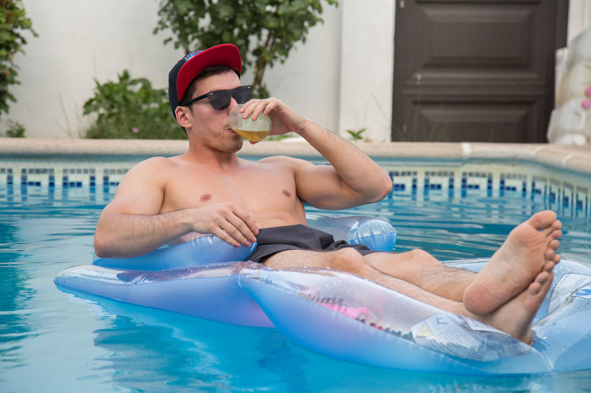 Young strong man drinking beer on an air bed in the pool. Beer Fun Happy Holiday Lifestyle Man Relaxing Air Bed Airbed Alcohol Cap Cheerful Drinking Enjoyment Party Pool Resort Rest Summer Sunbathing Swim Tan Vacation Water Young Adult