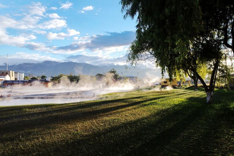 Steam coming out from hot water springs by field during sunny day