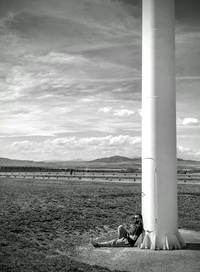 Man relaxing on field against sky