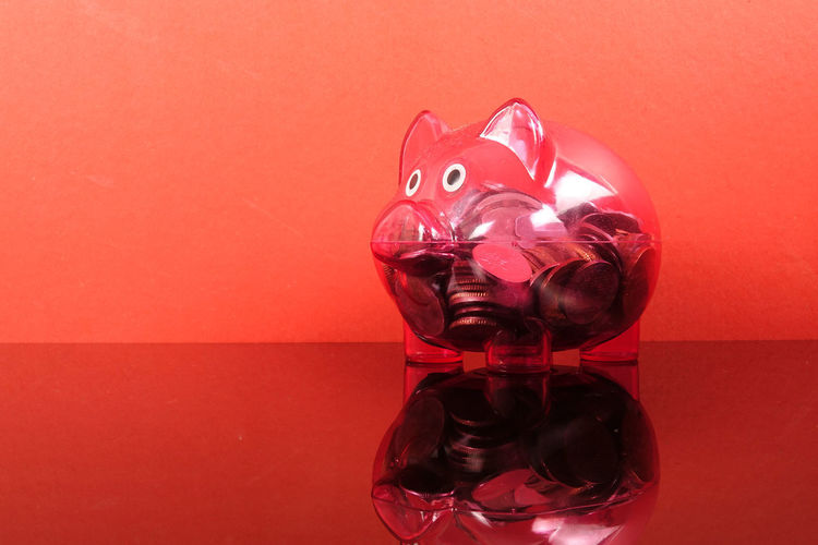 Saving concept with red piggy bank on red background. Piggy Bank Animal Representation Art And Craft Close-up Coin Colored Background Conceptual Photography  Copy Space Creativity Glass - Material Indoors  Investment Mammal No People Piggy Bank Red Representation Saving Concept Shape Still Life Studio Shot Table Toy Transparent Wall - Building Feature