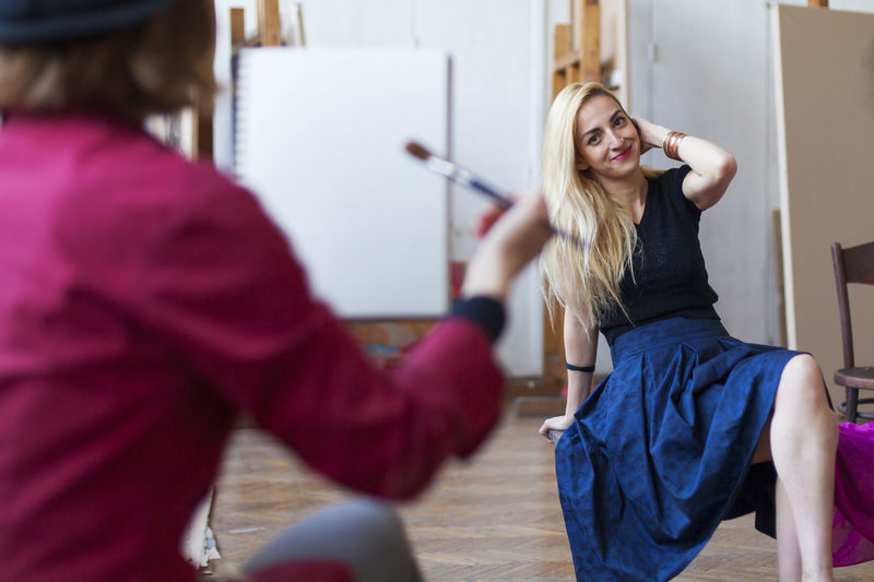 Smiling woman sitting indoors while getting painted at art studio