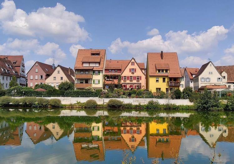 Houses by lake against buildings in city