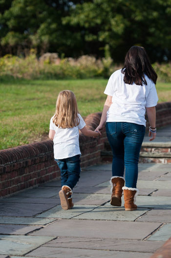 Two Young Girls Holding Hands and Walking Together Relationship Sisters Young Bonding Childhood Family Full Length Girls Leisure Activity Lifestyles Love Nature Outdoors People Real People Rear View Togetherness Young Women