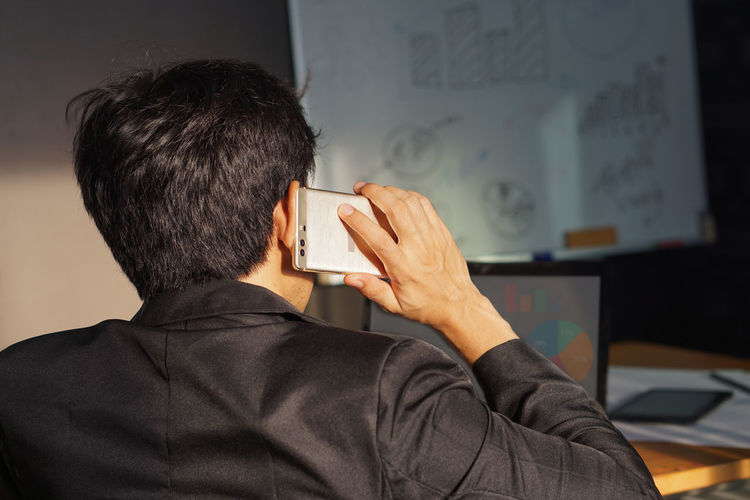 Rear view of man using mobile phone