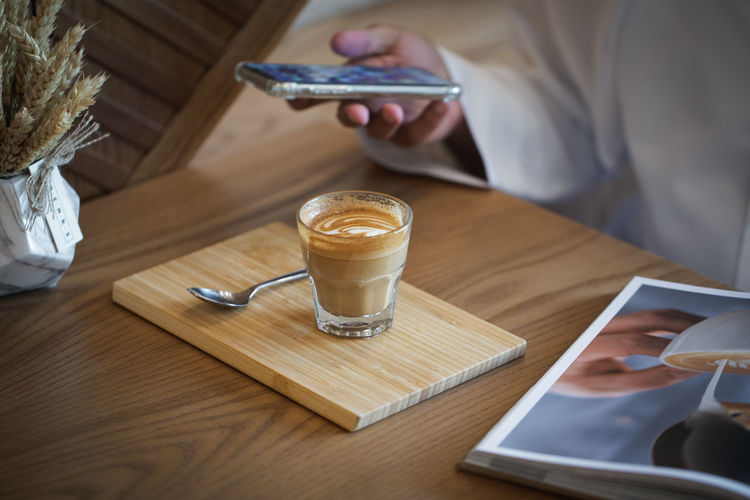 Coffee on Wooden Table with Book in Cafe Ijas Muhammed Photography Wireless Technology Technology Table Communication Coffee Food And Drink Connection Wood - Material Drink Holding Coffee - Drink Indoors  Mobile Phone Portable Information Device One Person Human Hand Real People Smart Phone Digital Tablet Refreshment Hand Glass