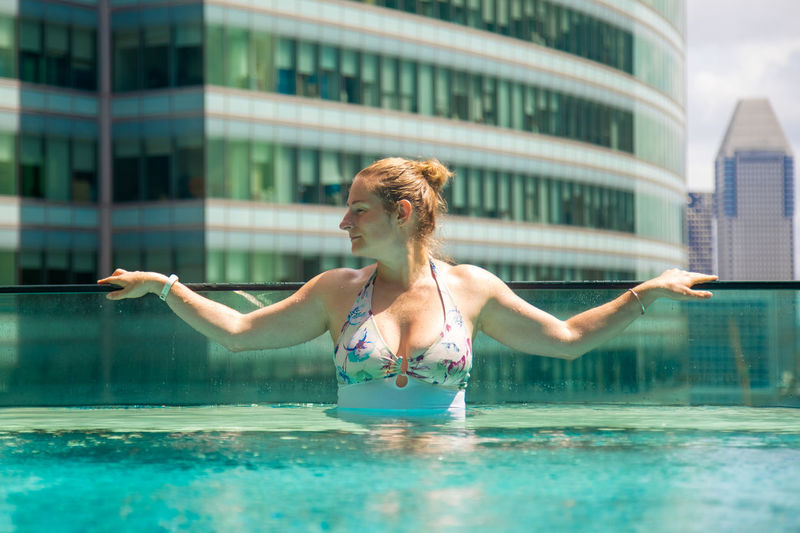 Woman with swimming pool in city