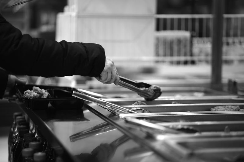 Cropped hands of man serving food at market stall
