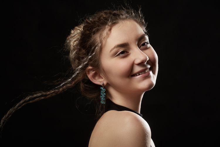 Portrait of smiling woman against black background