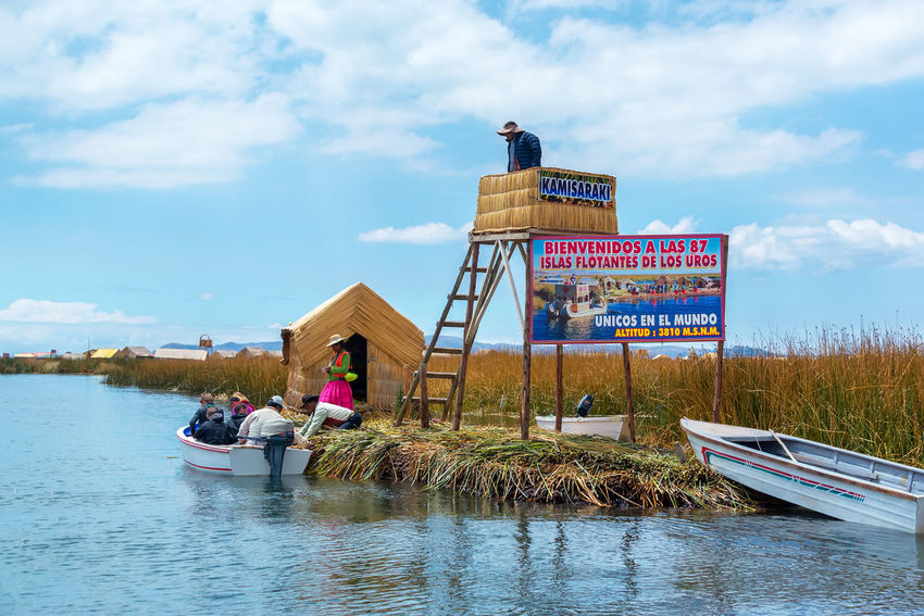 PUNO, PERU - SEPTEMBER 18: Entrance and control office to the Uros Floating Islands near Puno, Peru on September 18, 2014 Aymara Day Floating Indigenous  Island Islands Lake Titicaca Man Made Object Manmade Nautical Vessel Peru Puno Real People Reed Reeds Sky Totora Tourism Travel Travel Destinations Uros Uros Island Uros Island - Lake Titicaca Uros Islands Uros Islands - Titicaca Lake