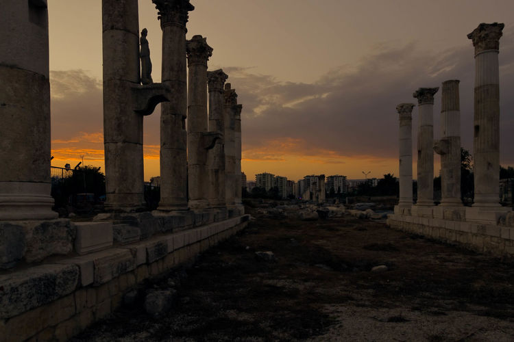 Low angle view of old columns against cloudy sky at mezitli
