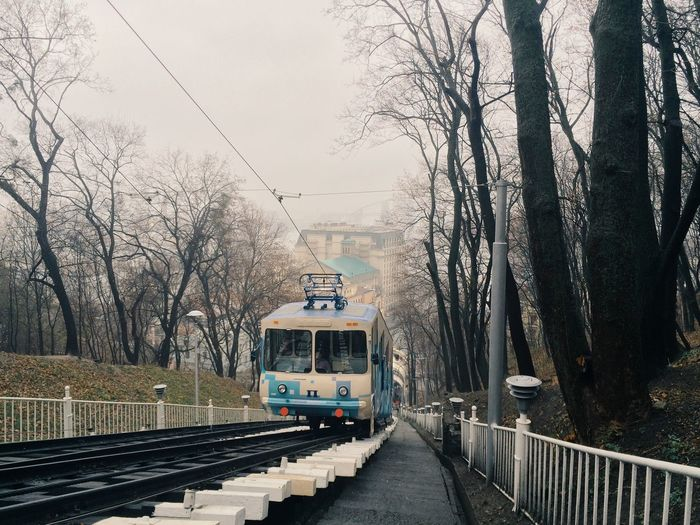 Tram Moving Amidst Bare Trees In City Against Sky