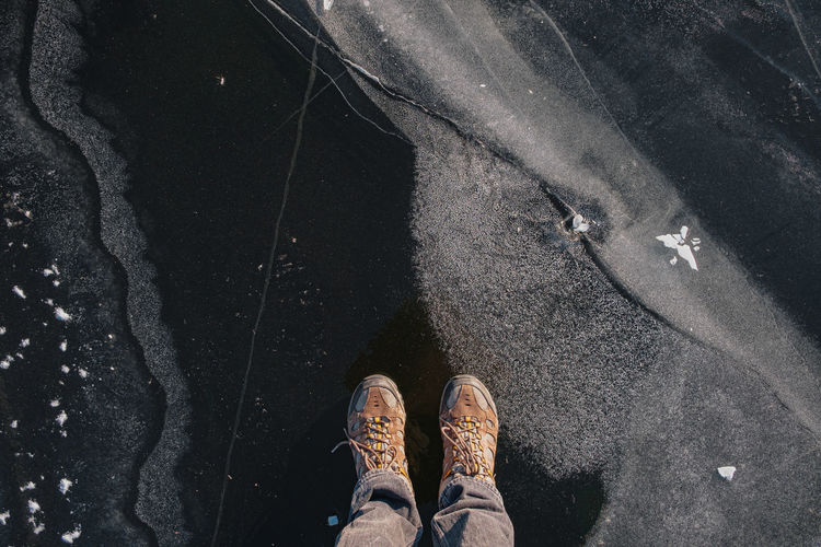 Low section of person standing on frozen lake
