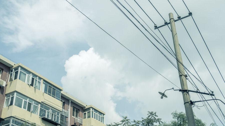 一座旧楼天天过,几根电线总当空,绿叶枝头寻常见,添朵白云便不同。 clous Cloud - Sky Low Angle View Power Line  Built Structure Tree Building Day No People