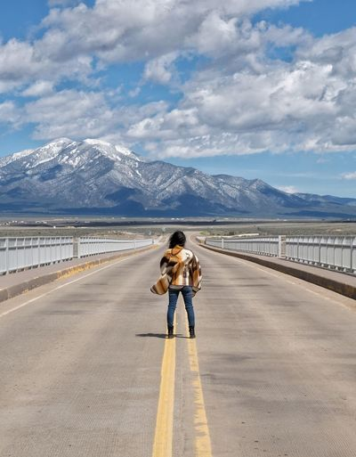 Rear view of woman on road against mountain range