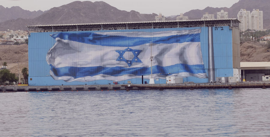 Israeli flag at the Red Sea port of Eilat Eilat Israeli Flag Israeli Flags Architecture Building Exterior Built Structure Clothesline Day Drying Hanging Israel Mountain No People Outdoors Port Of Eilat Red Sea Water