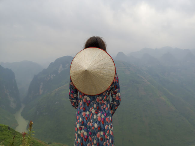 Young Vietnamese women facing and pose for camera with stunning view of the Nho Que river surrounded by mountains from the Ma Pi Leng pass in northern Vietnam Mountain Cloudy Green Color Meo Vac Vietnam Vietnamese Adult Ao Dai Beauty In Nature Casual Clothing Fog Idyllic Landscape Leisure Activity Lifestyles Looking At View Mountain Mountain Range Nature Non-urban Scene One Person Outdoors People Pose Real People Rear View Scenics - Nature Standing Sunrise Traditional Dress Tranquil Scene Tranquility Valley Warm Clothing Women
