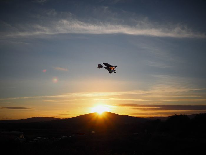 Low angle view of light aircraft flying over silhouette mountains during sunset