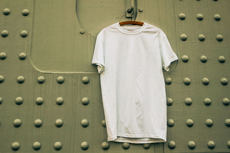 Close-Up Of T-Shirt Hanging Against Patterned Wall