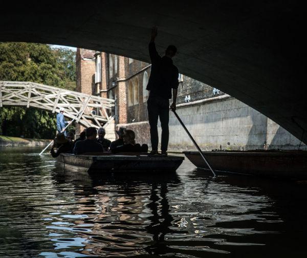 Silhouette people on bridge over river