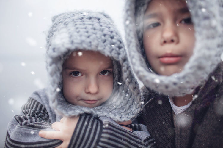 Portrait of cute smiling siblings outdoors during winter