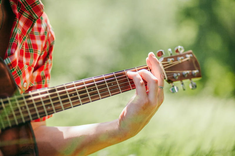 man playing guitar outdoors in park at summer Musical Instrument Music Playing String Instrument Arts Culture And Entertainment Musical Equipment Human Hand Guitar One Person Musician Holding Plucking An Instrument Leisure Activity Outdoors Finger Acoustic Guitar String Summer Village Countryside Hand Adult Artist