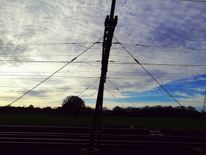 Embrace Urban Life Electricity  Power Supply Power Line  Connection Cloud - Sky Silhouette Sky No People Cable Outdoors Low Angle View Technology Tree Nature Electricity Pylon Sunset Iron - Metal Travel Public Transportation Railroad Transportation Finding New Frontiers