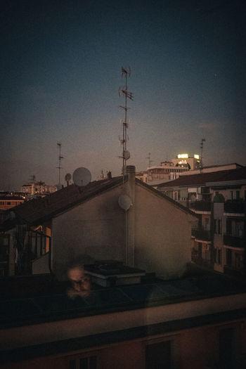 Street amidst buildings against sky at dusk